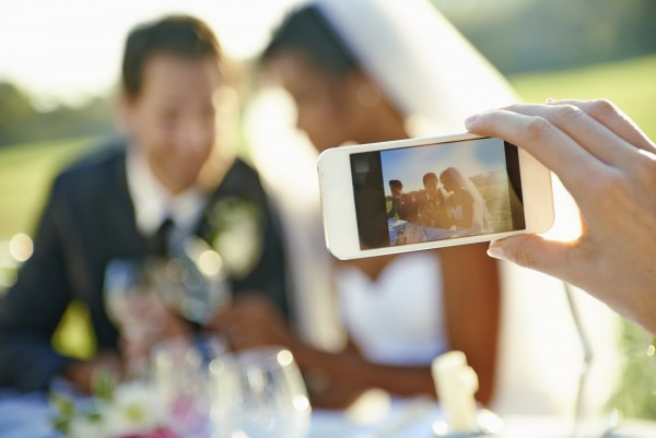 Shot of a wedding guest taking a photo of the bride and groom will a cellphone