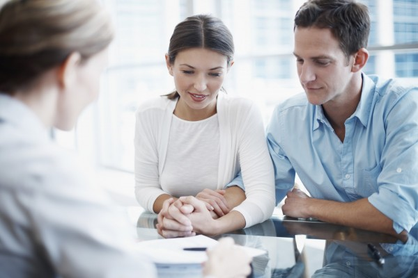 Shot of a consultant explaining a document to a young couple