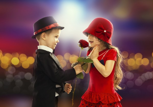 Lovely little boy giving a rose to fashionable girl and her excited