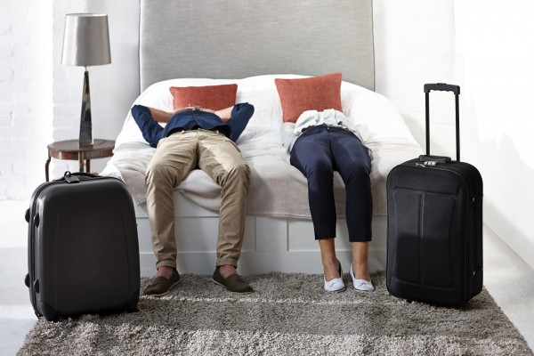 Indoor shot of mature couple lying on bed with luggage