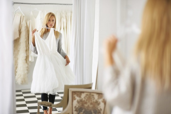 A young bride looking at her reflection in a mirror while choosing a dress