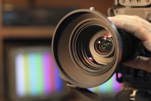 Closeup shot of professional video camera, with its lens zooming in.