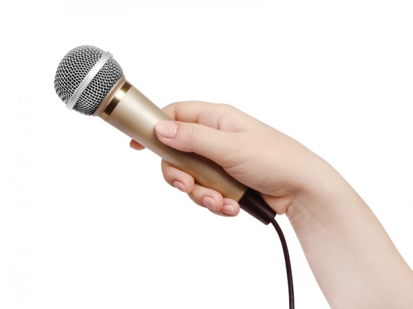 Female hand with microphone, on white background.
