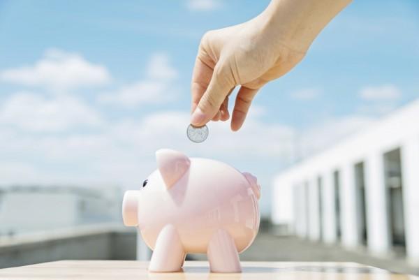 Human hand insert a coin in a pink piggy bank.