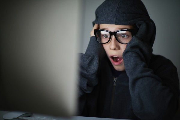 Frustrated boy with open mouth looking computer screen