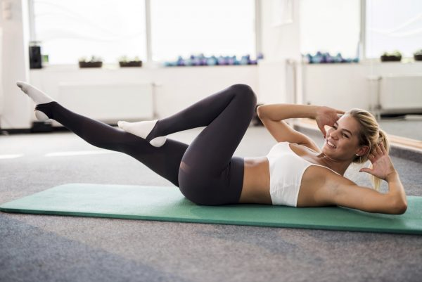 Happy woman doing sit-ups on exercise mat during a sports training.