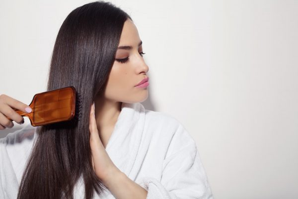 beautiful young woman combing her healthy and shiny hair, studio white
