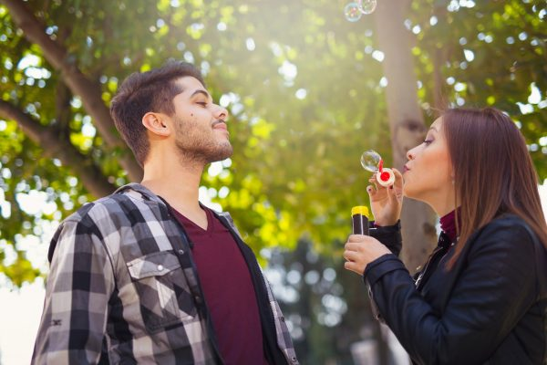 Couple Relaxing in the Park with bubble blower. Spring time.