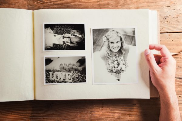 Picture of bride and groom in photo album. Studio shot on wooden background.