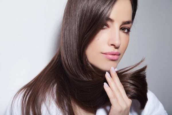 beautiful young woman holding her healthy and shiny hair, studio white
