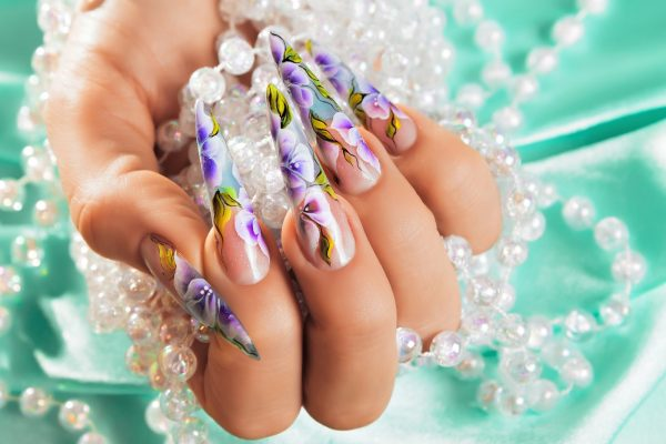 Female hand with beautiful floral design on nails.