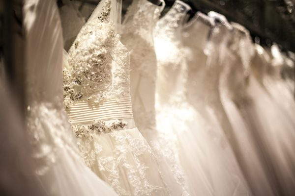 A shopping rack full of white wedding dresses with different styles and sizes.