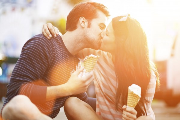 romantic couple kissing while holding ice cream