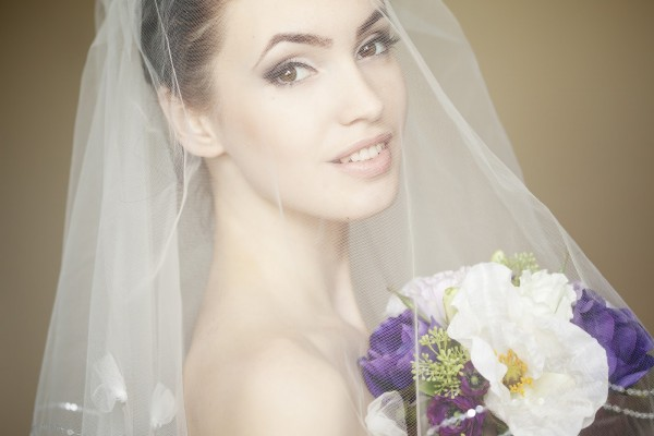 Portrait of a fresh and lovely bride wearing veil and smiling