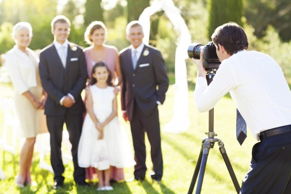 Young man photographing family at outdoor wedding. Horizontal shot.