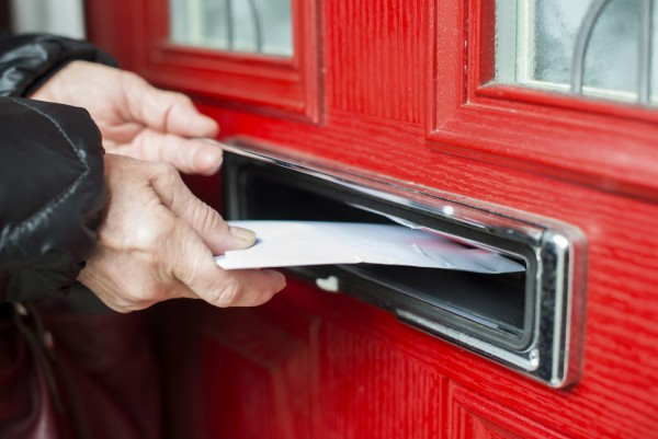 Hand putting Letter in a red mailbox.