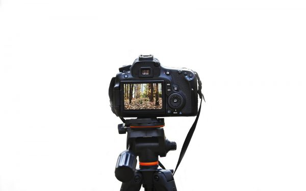 Tripod and camera isolated on white background.