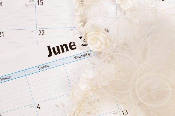 June calendar with bridal wedding veil. Summer weddings concept.