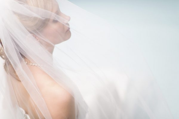 Close up beautiful lonely bride, light blue background, horizon format