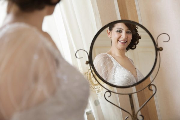 bride smiles in front of the mirror