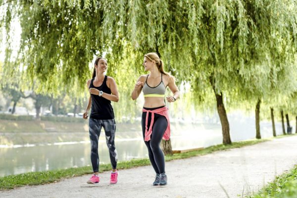 Women (25, 30s) quickly walking in park, power walking.