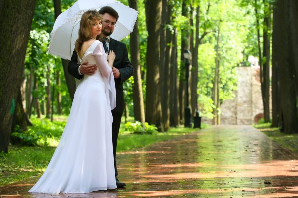 Just married ride and groom under rain