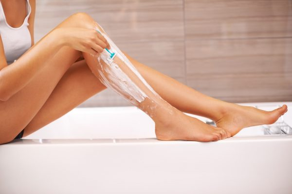 Cropped view of a woman shaving her legs