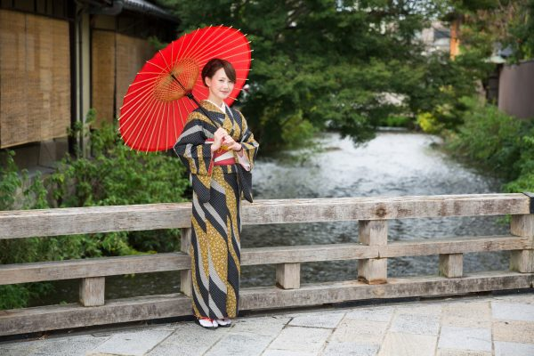 Japanese woman in traditional kimono holding an umbrella