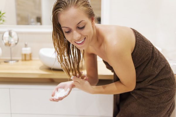 Woman applying conditioner after the shower