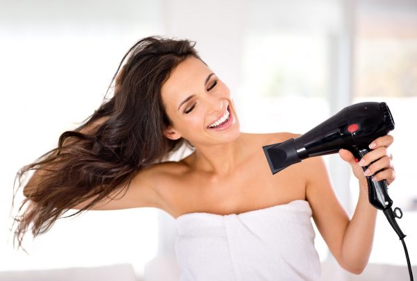A beautiful woman smiling while drying her hair with a hairdryer