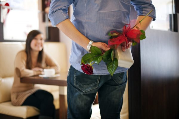 Young man giving a gift and flower his girlfriend on Valentine's Day